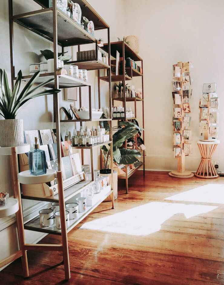 An inside of a stationery store with greeting cards and vases placed inside.