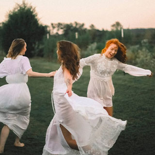 3 girls in white dresses dancing in a circle on a grass field.