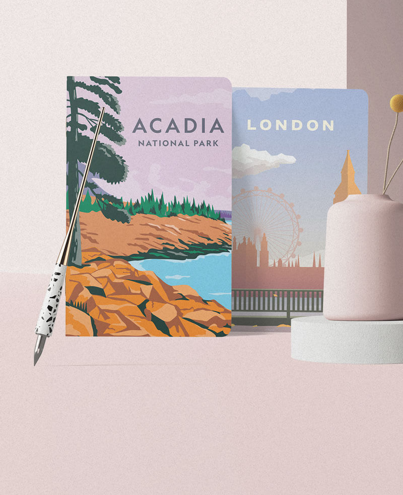 Two notebooks with Acada National Park and London city illustrated on it, leaned on a pink wall, next to a pink vase.