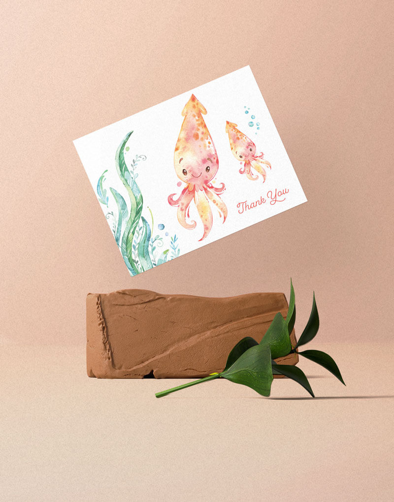 A greeting card with mother and baby squid illustration. Placed with the angle on top of an orange rock with a green branch in front of it.