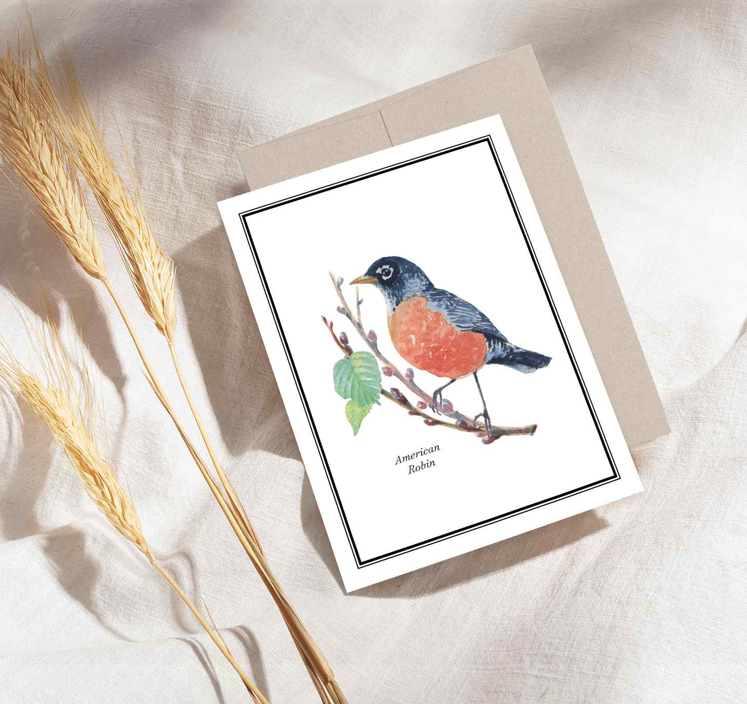 Red and black bird sitting on brown branch design with brown envelope