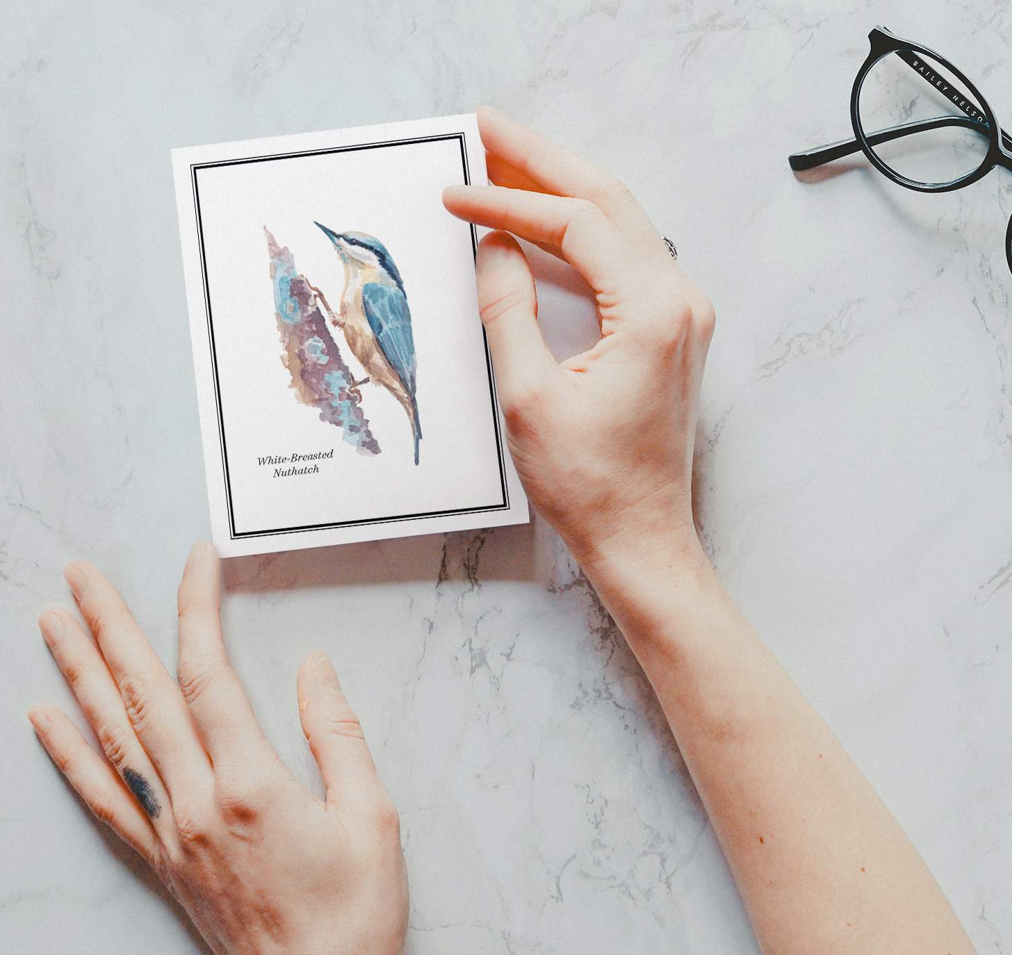 Woman's hand holding card with Blue and white bird sitting on brown branch with marble background