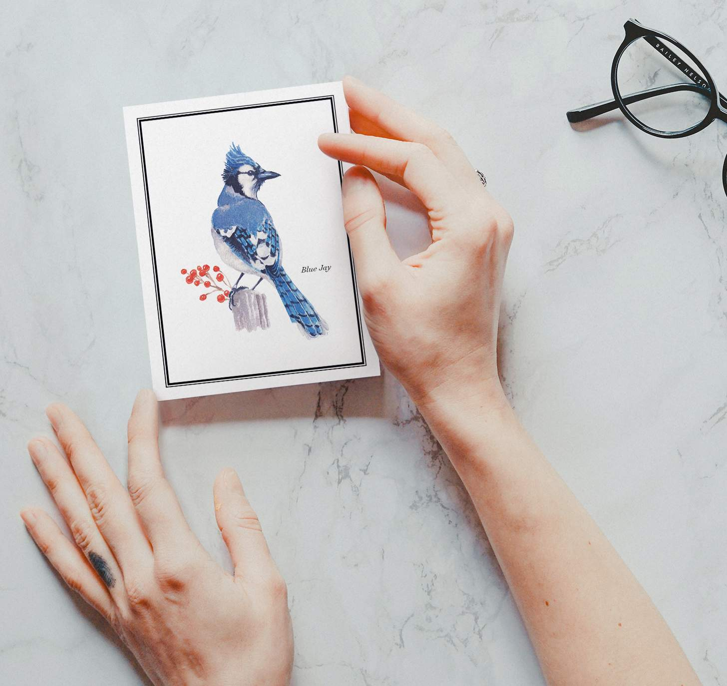Woman's hand holding card with Blue and white bird sitting on stump with marble background