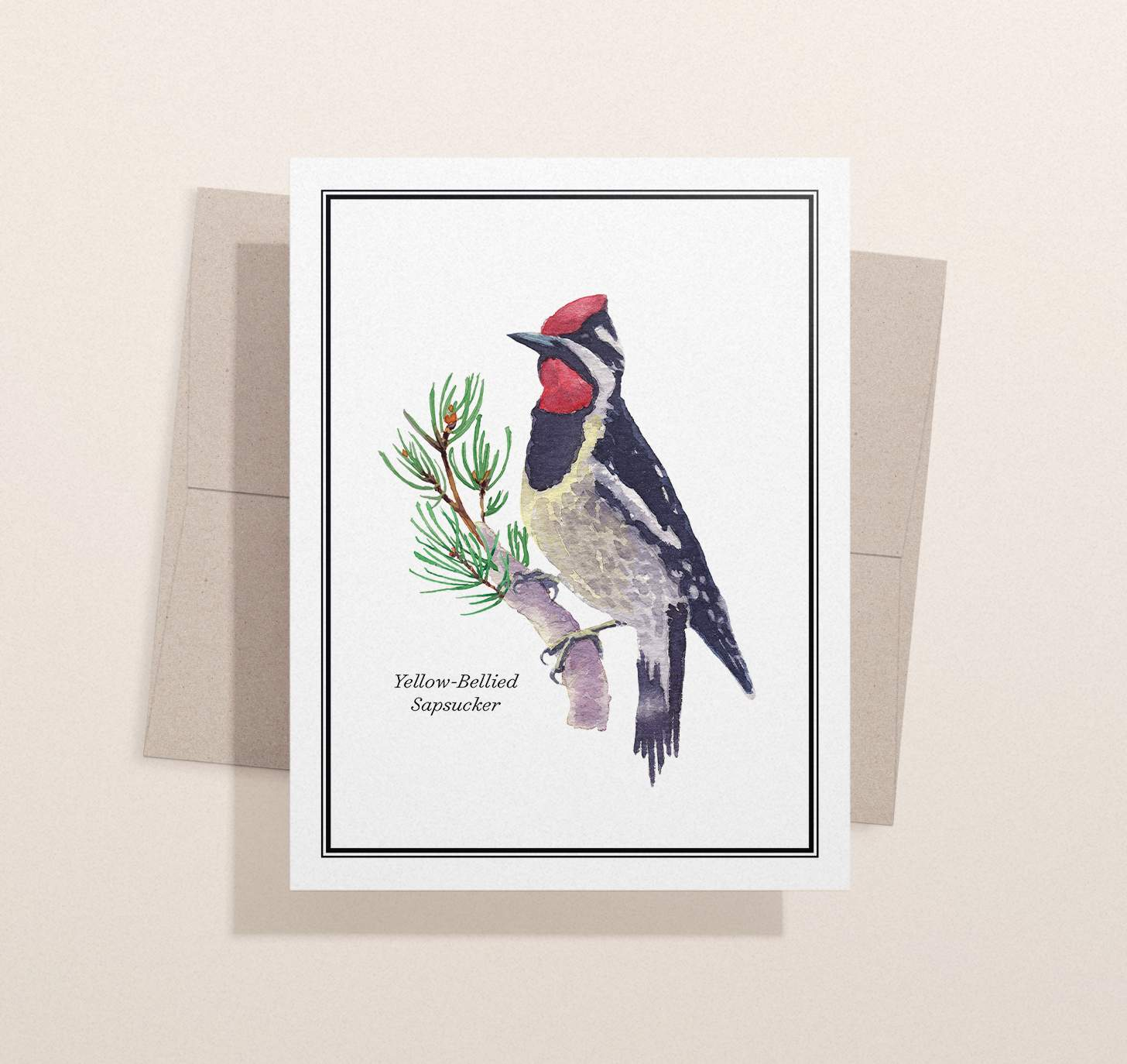 Red, black and gray bird sitting on pine branch design with envelope and light brown background