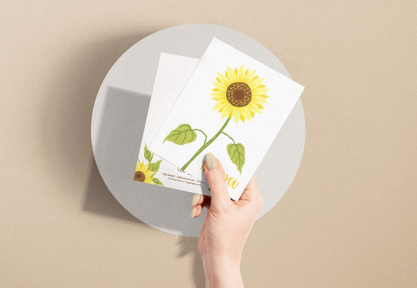 Hands holding yellow sunflower design with brown background