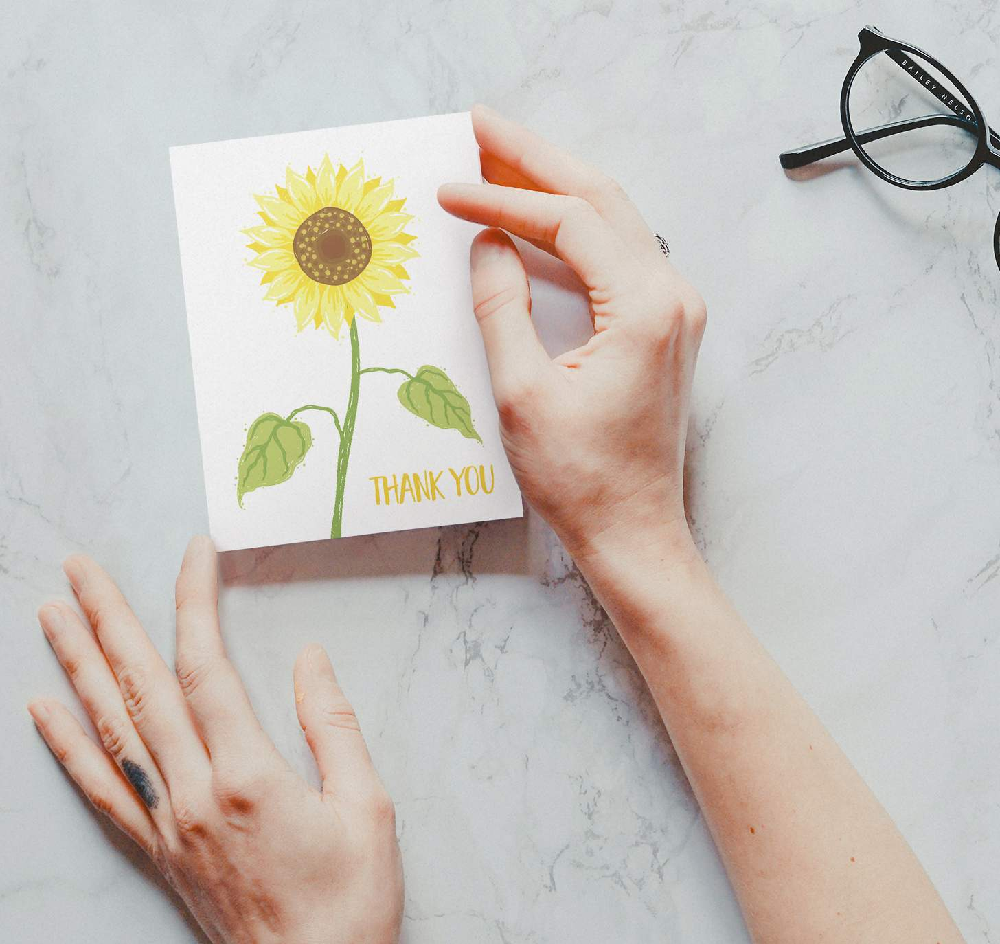 Hands holding yellow sunflower design with marble background