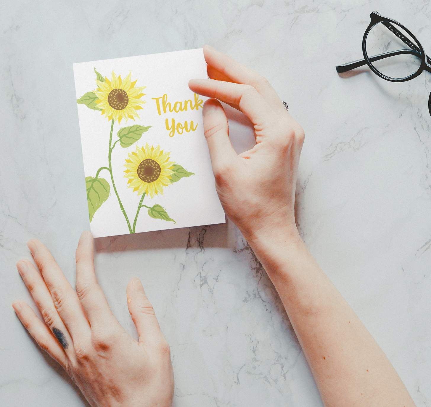 Hands holding Two yellow sunflower design with marble background