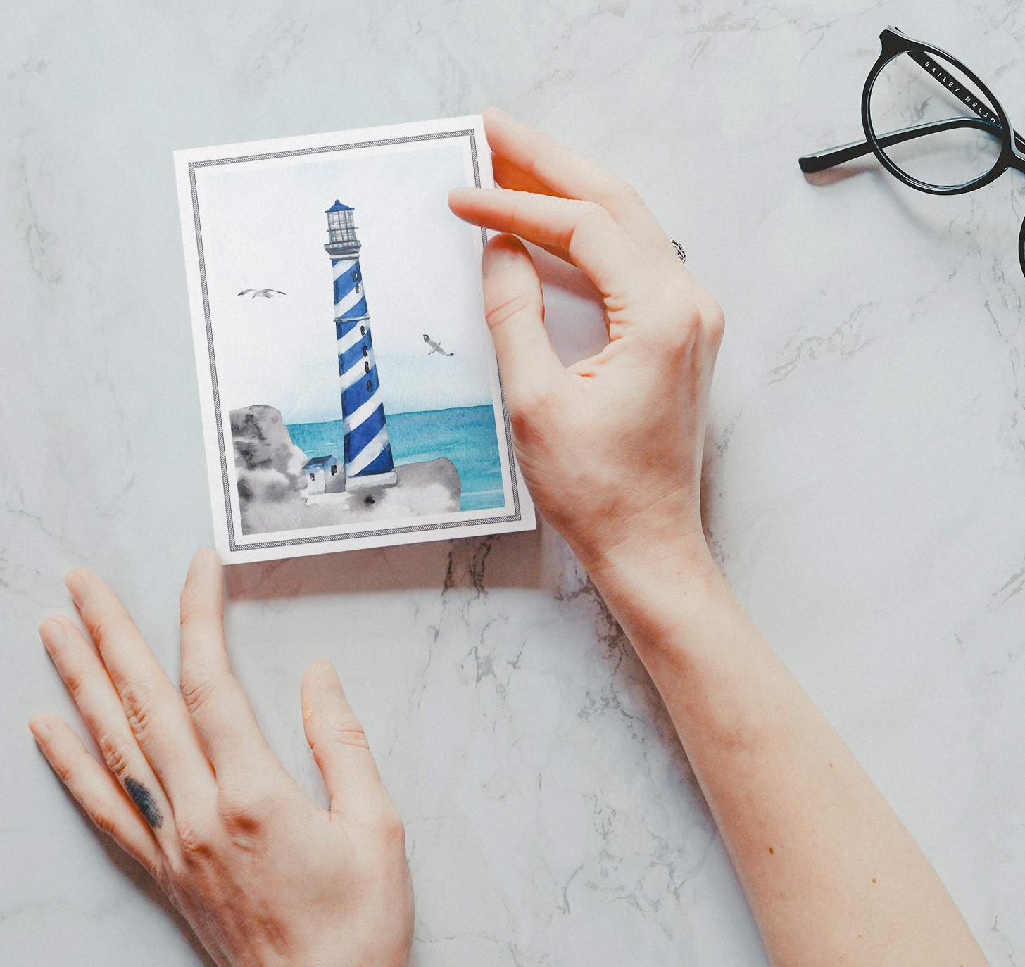 Hands holding blue striped lighthouse design with ocean card with marble background