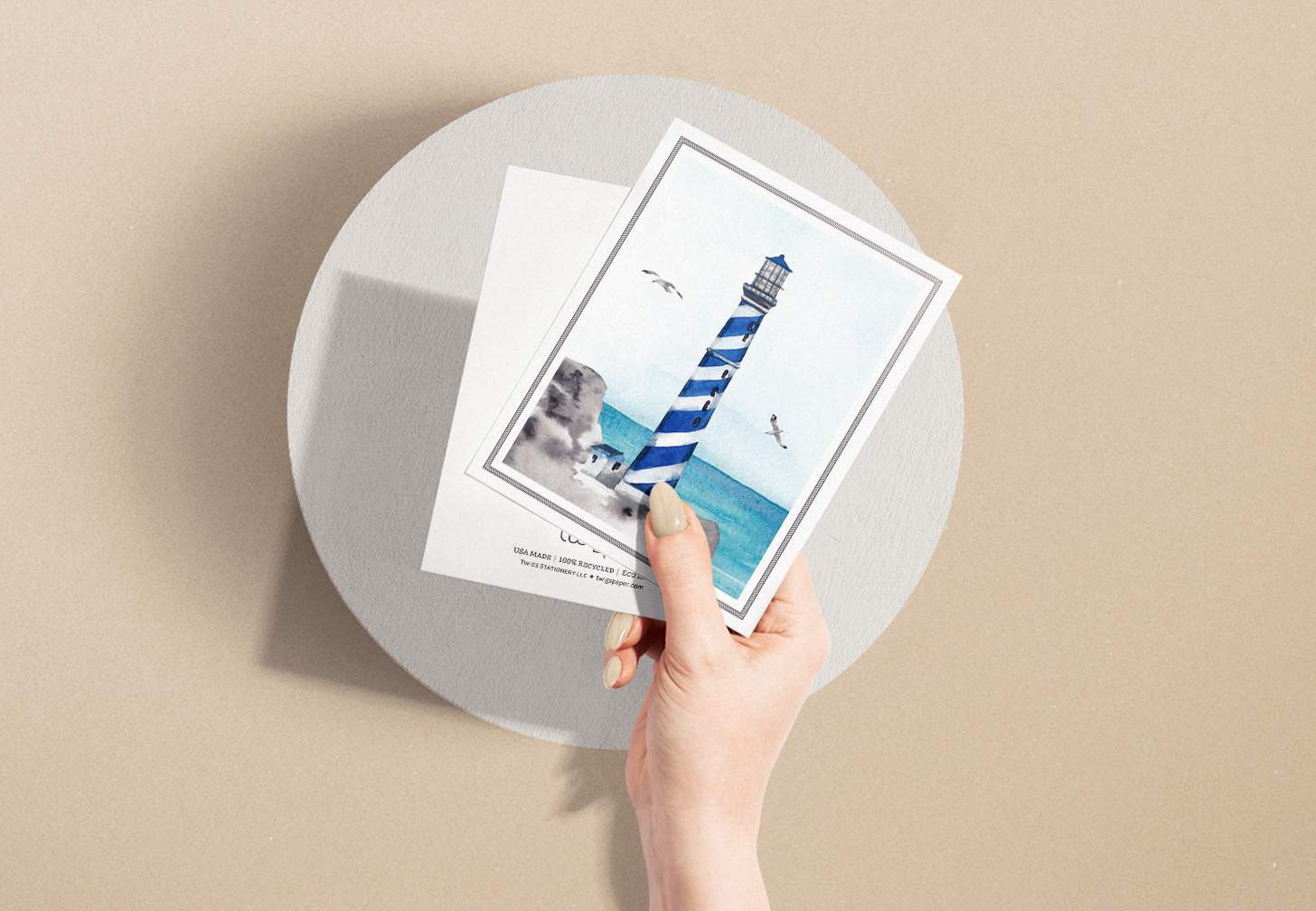 Hands holding blue striped lighthouse design with ocean card