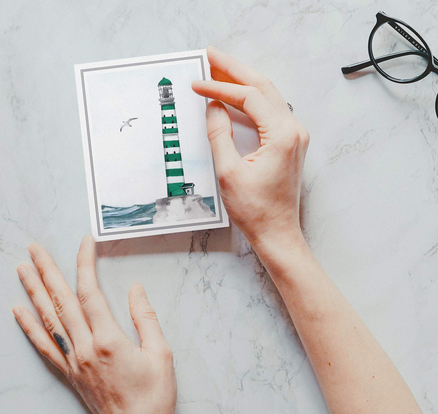 Hands holding Green striped lighthouse design with ocean card with marble background