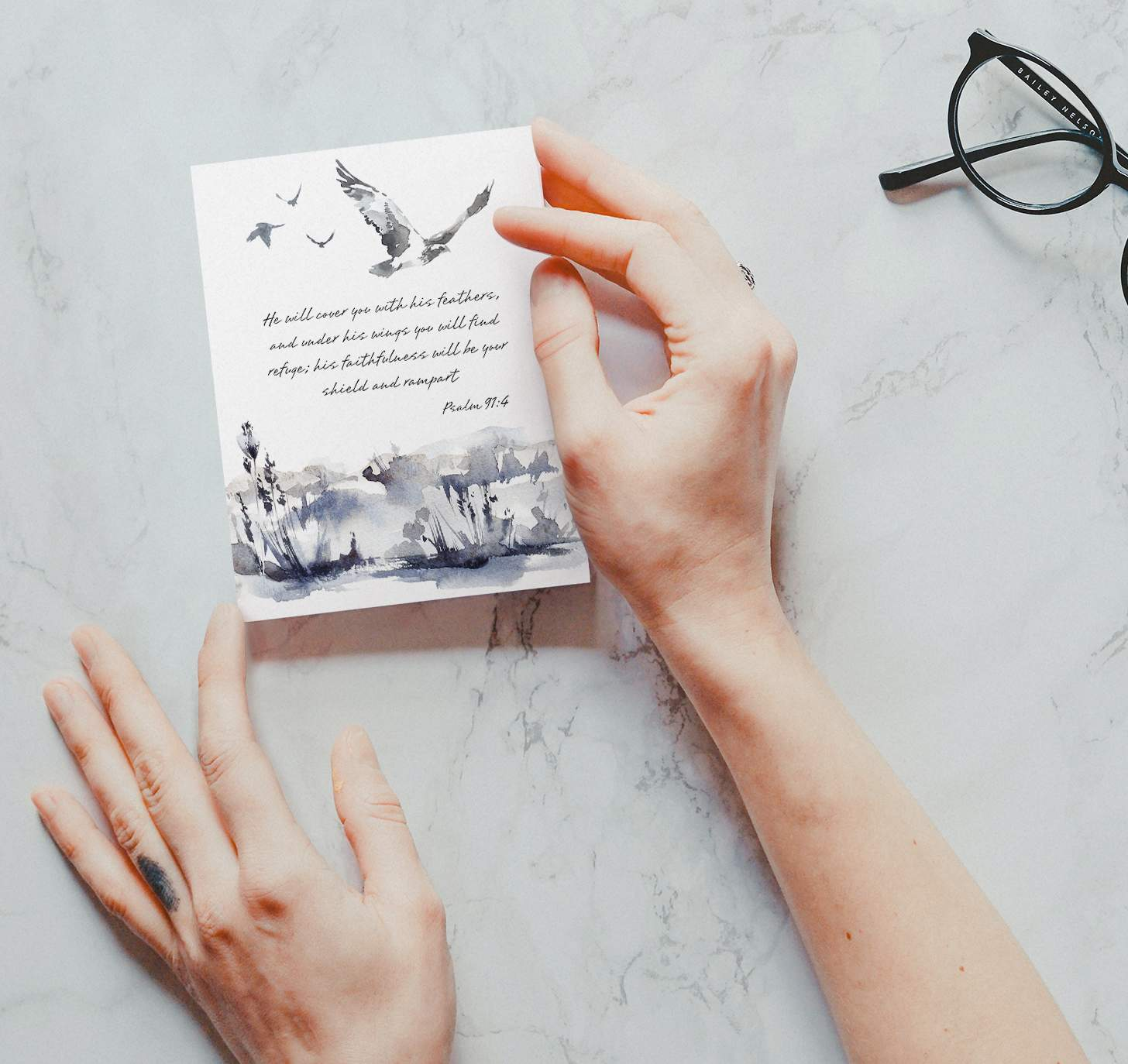 Hands holding Gray bird themed sympathy design on marble background