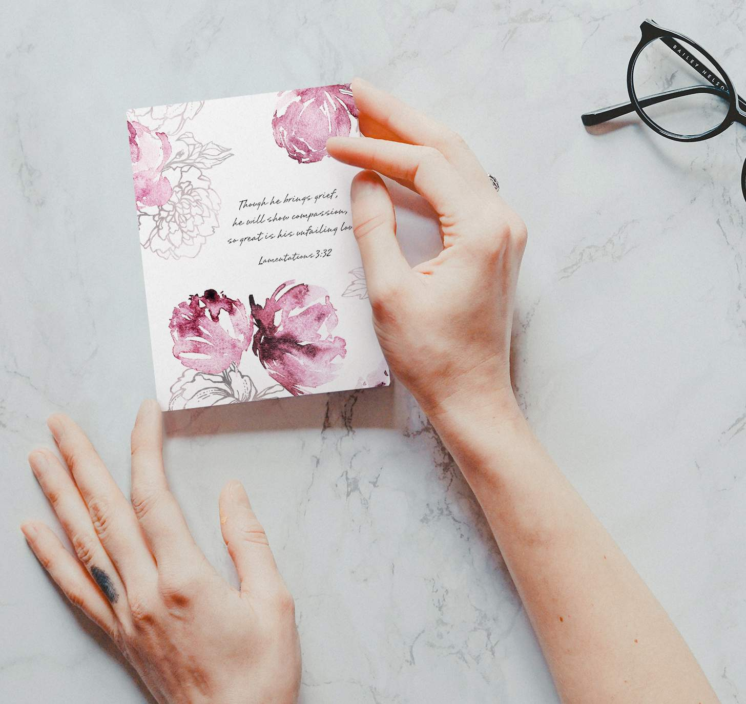 Hands holding Pink floral themed sympathy design on marble background