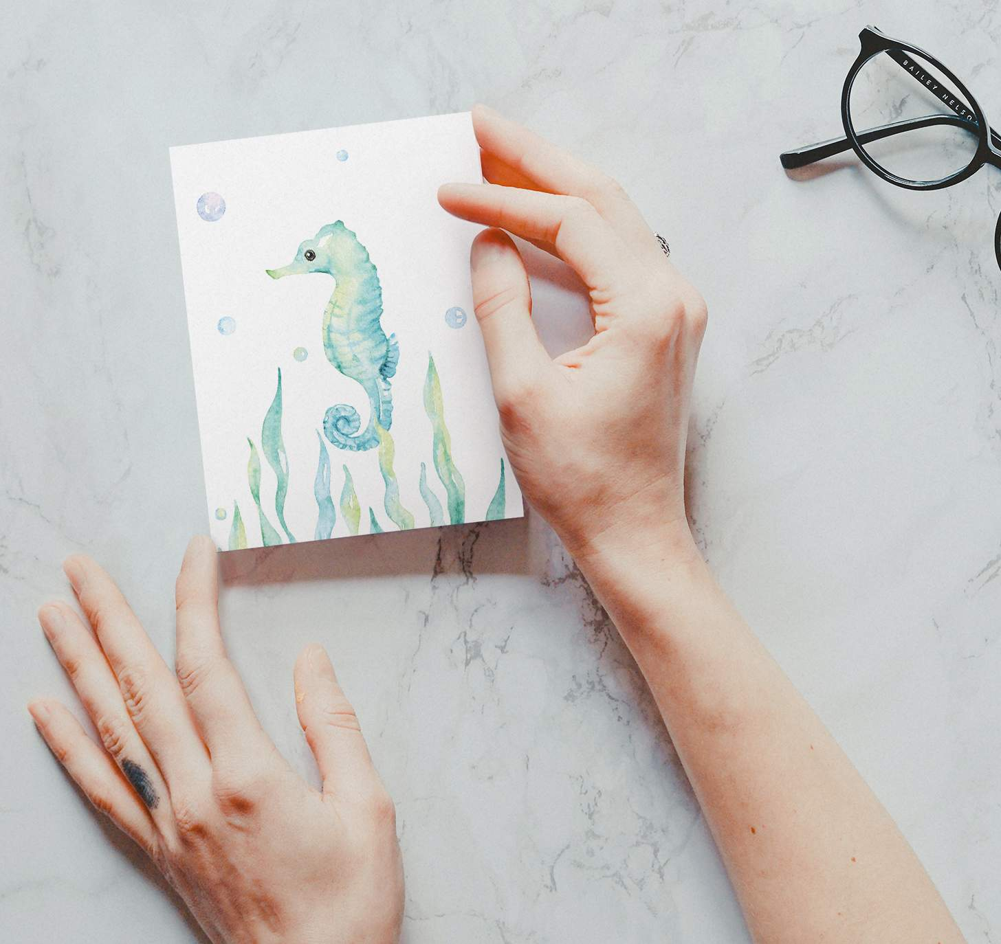 Woman's hand holding Turquoise seahorse swimming