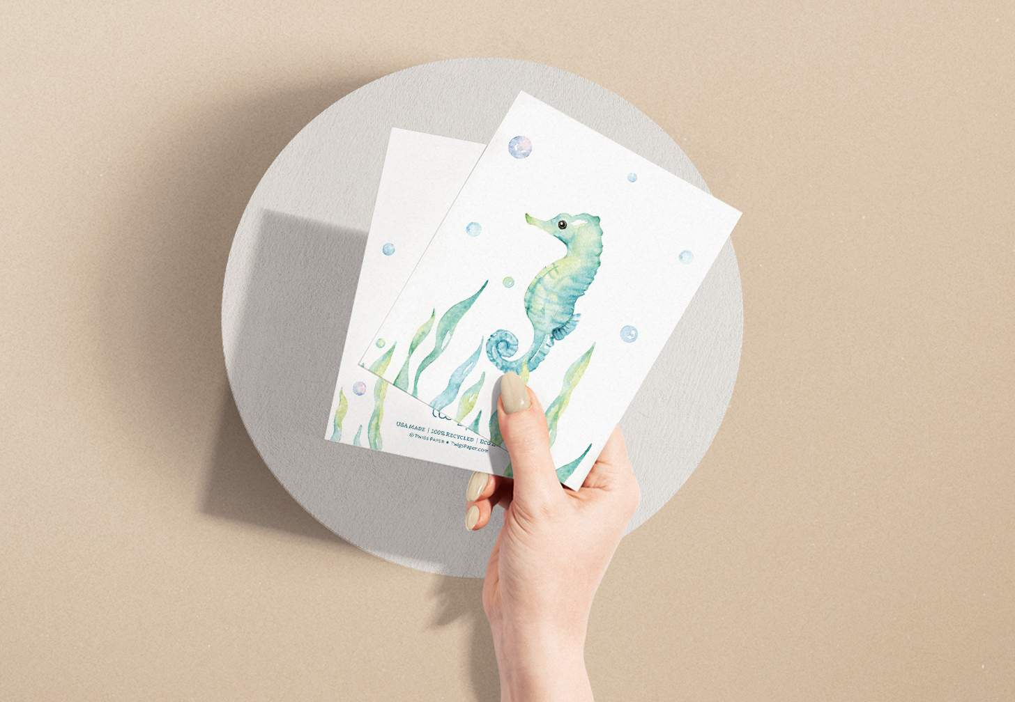 Woman's hand holding two cards with Turquoise seahorse swimming