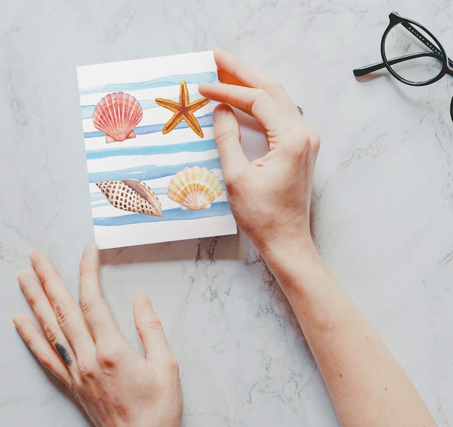 Woman's hand holding watercolor seashells design