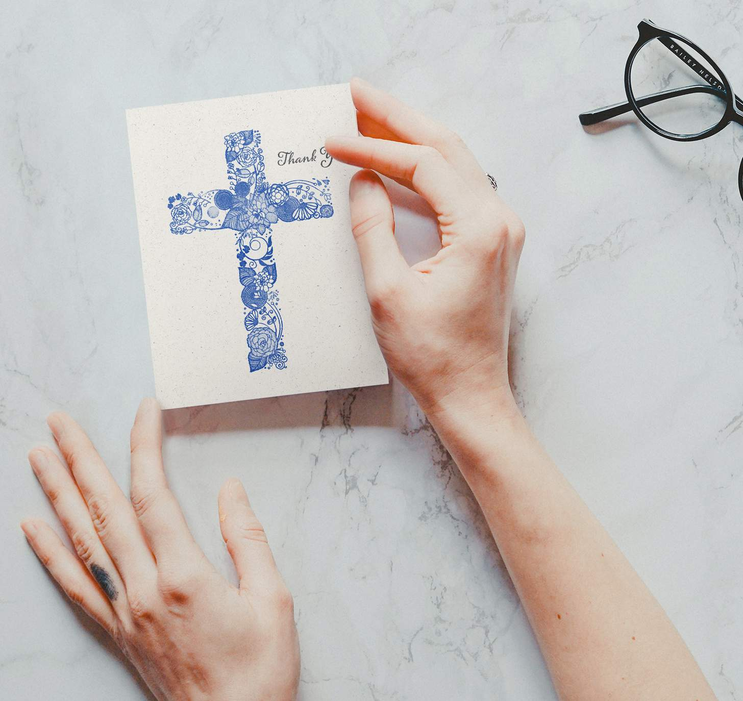 Woman's hand holding card with blue floral cross design on marble background