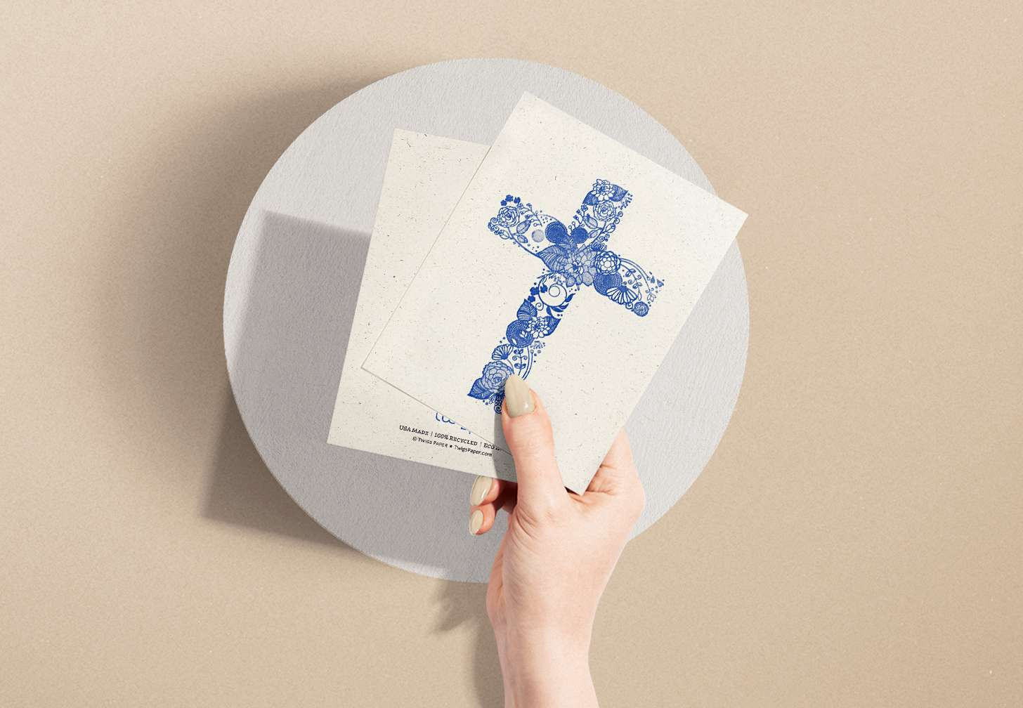 Woman's hand holding card with blue floral cross design
