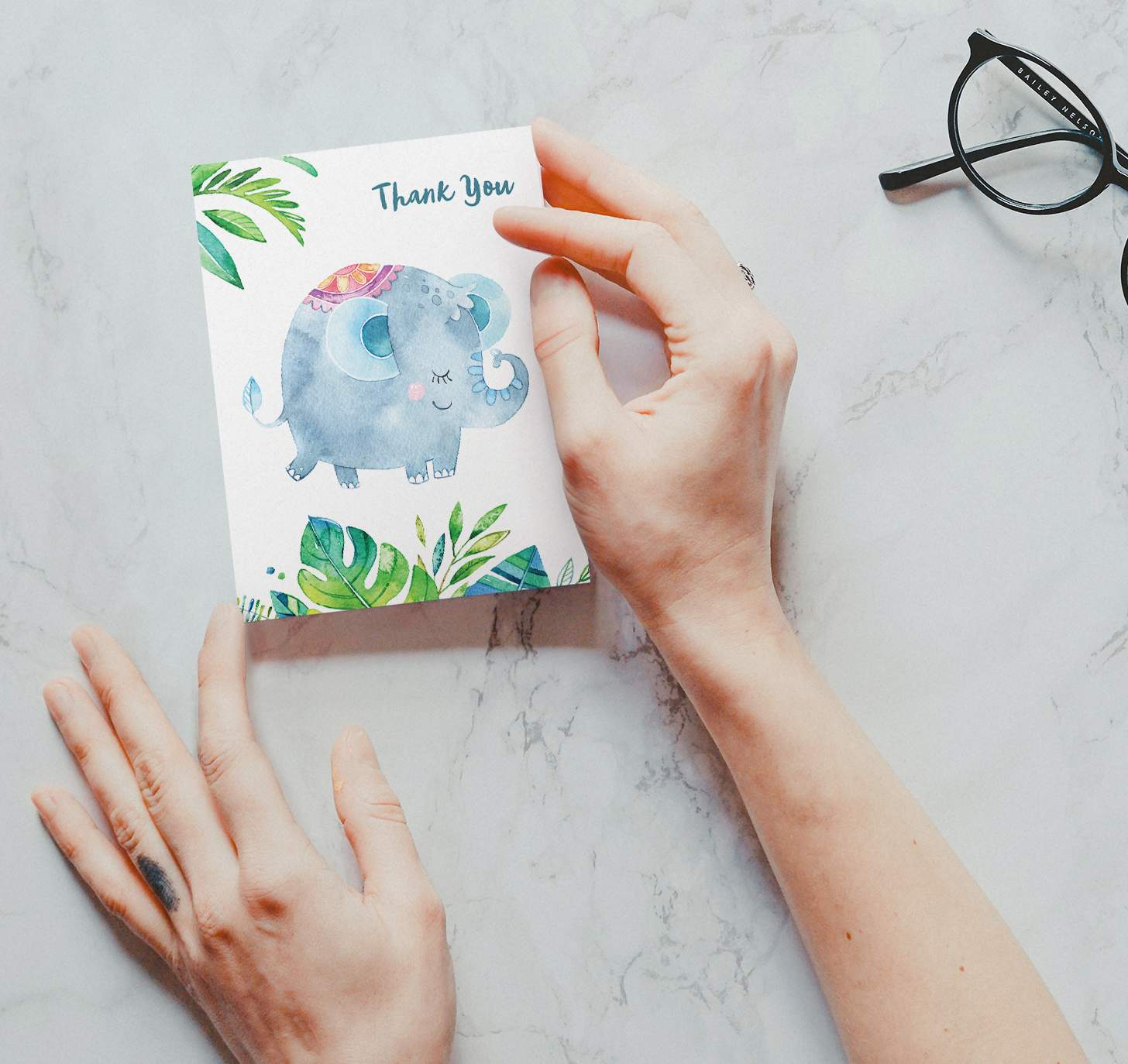 Woman's hands holding card with a cute blue elephant and green leaves design on a marble background