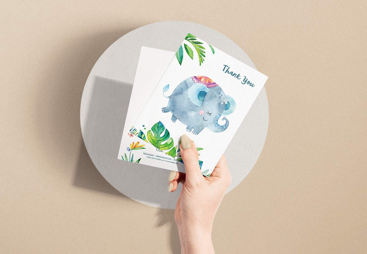 Woman's hand holding card with a cute blue elephant and green leaves design with a white envelope