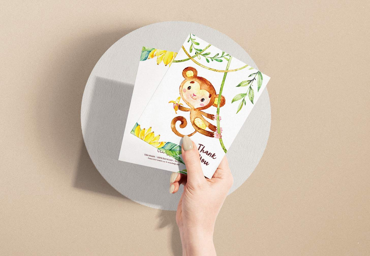 Woman's hand holding card with a cute brown monkey and tree design with a white envelope