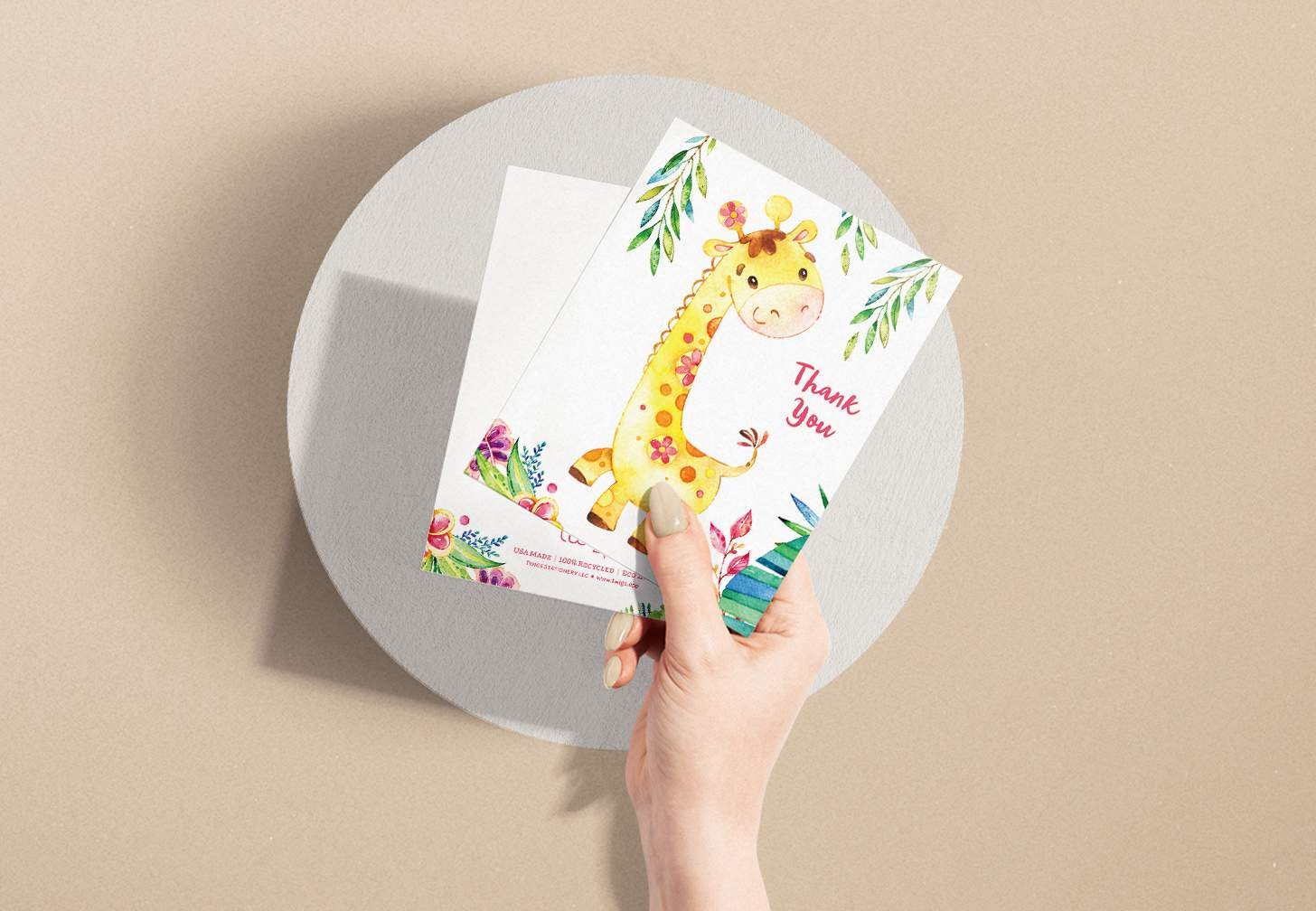 Woman's hand holding card with a cute yellow giraffe and plants design with a white envelope