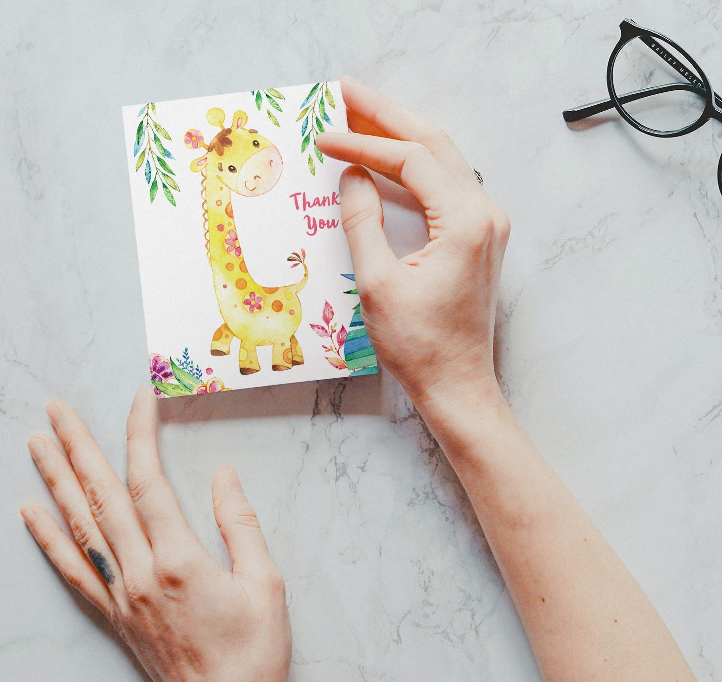 Woman's hands holding card with a cute yellow giraffe and plants design on a marble background