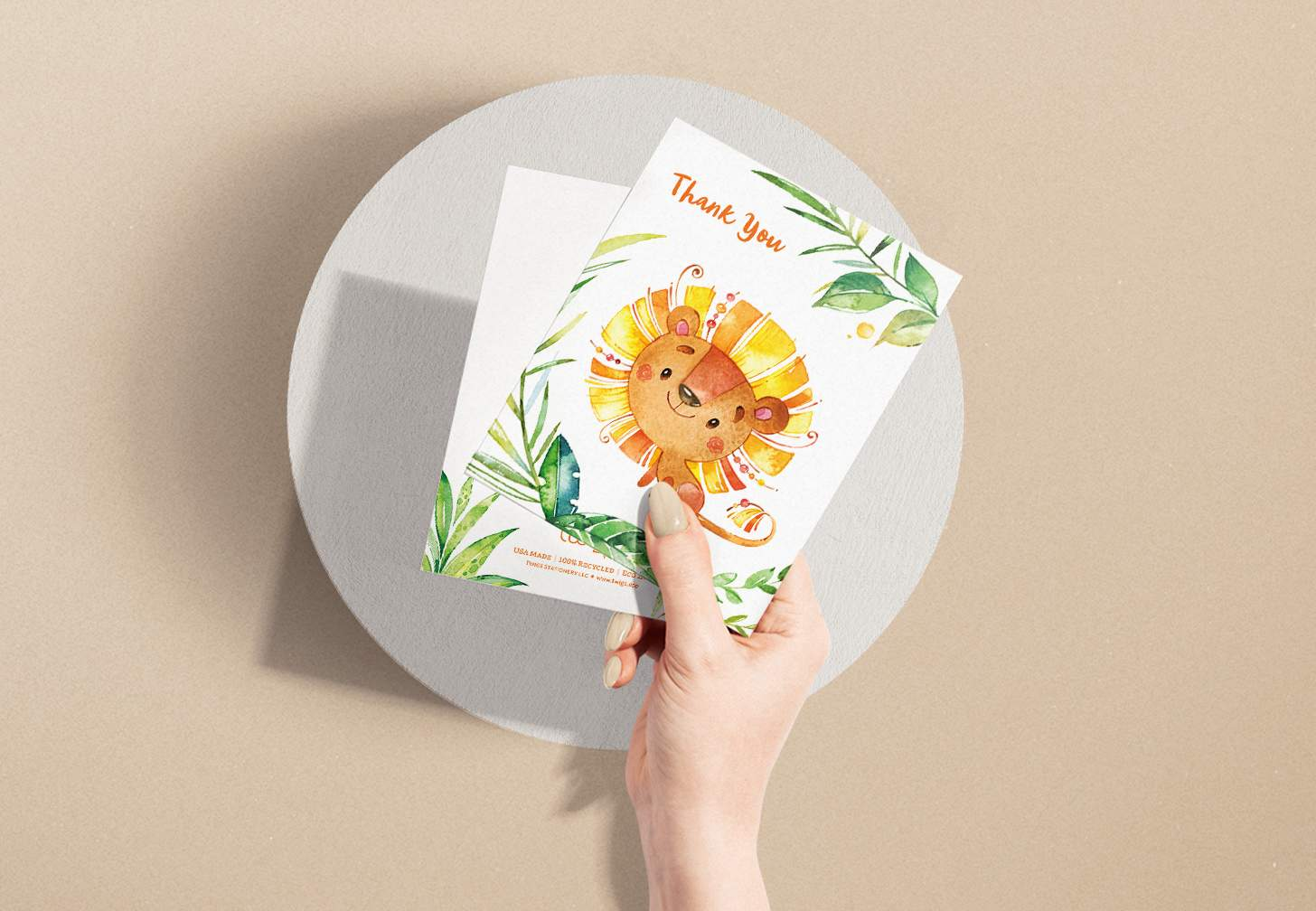 Woman's hand holding card with a cute orange and yellow lion and plants design with a white envelope