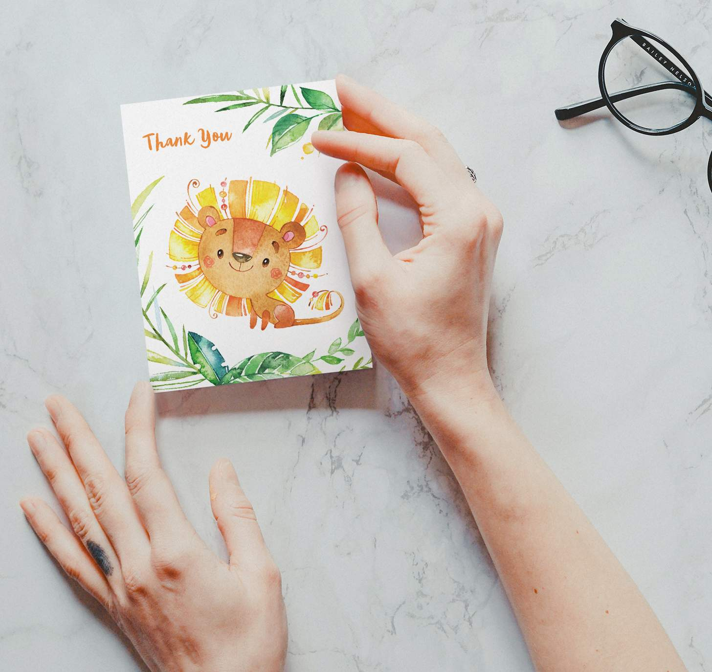 Woman's hands holding card with a cute orange and yellow lion and plants design on a marble background