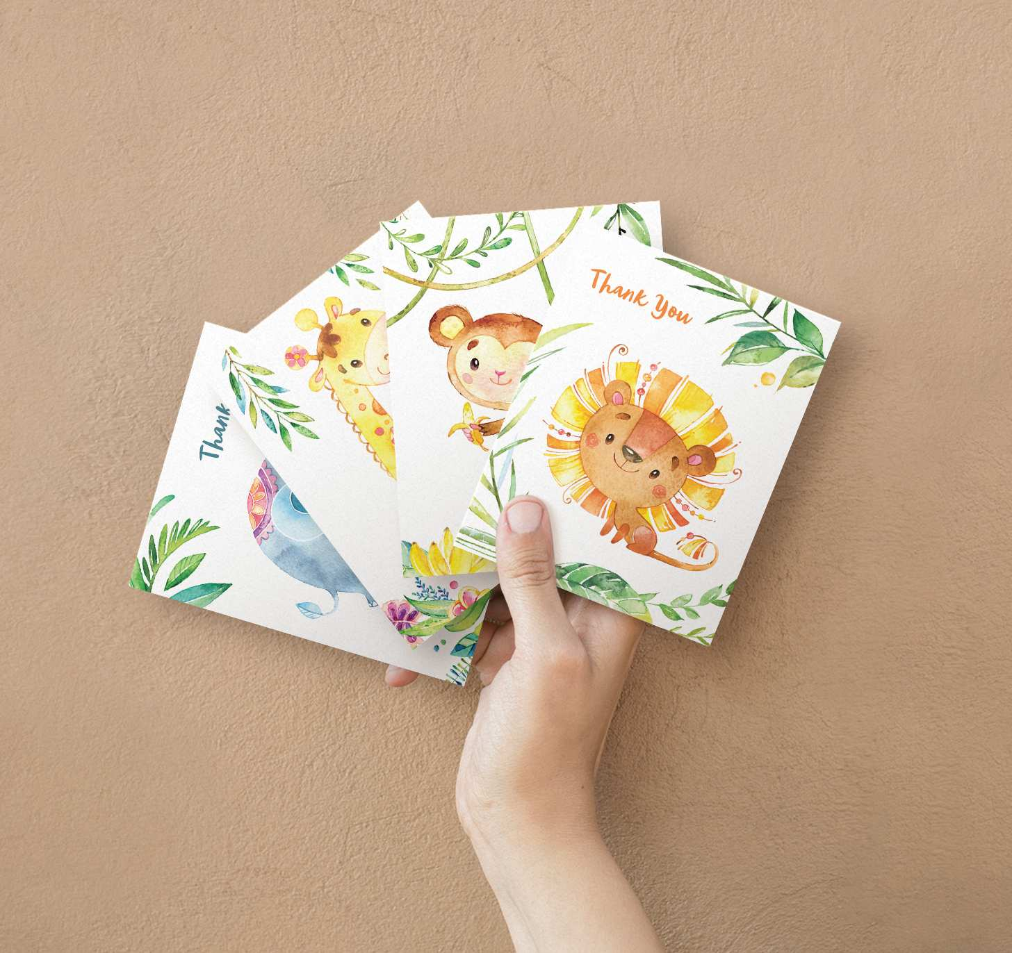 Woman's hand holding four overlapping cards with cute lion, monkey, giraffe, and elephant designs