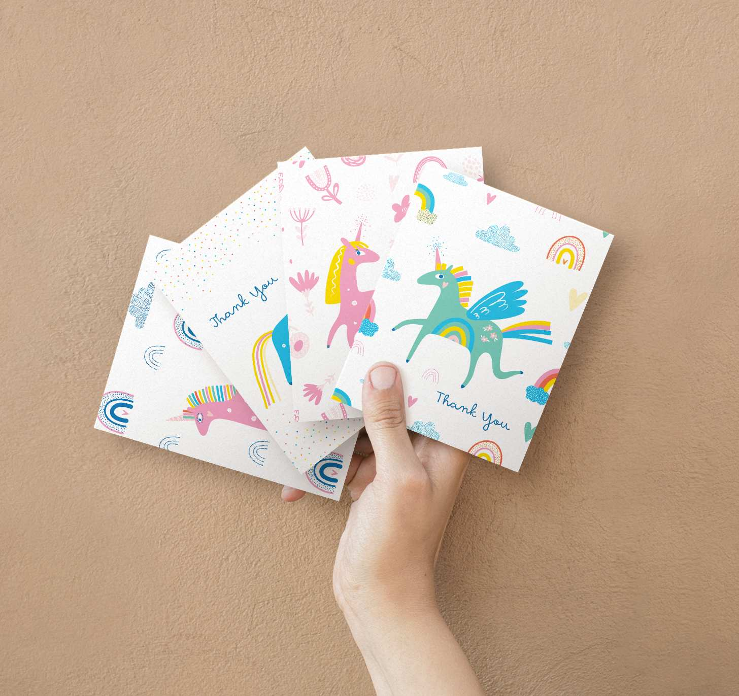 Hands holding four overlapping unicorn cards with assorted designs
