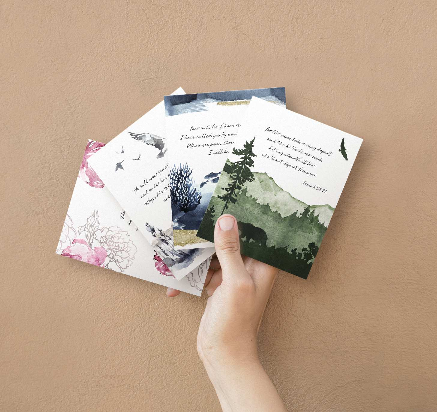 Hands holding four overlapping sympathy cards with pink, green, blue, and gray themes