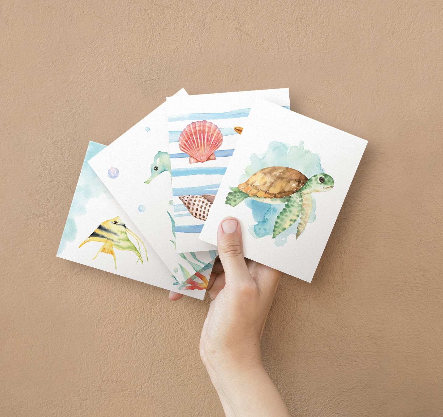 Woman's hand holding four overlapping cards with sea turtle, seahorse, seashells, and fish designs