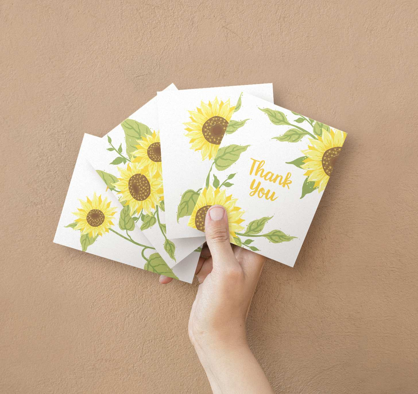 Hand holding four overlapping assorted yellow sunflower designed cards