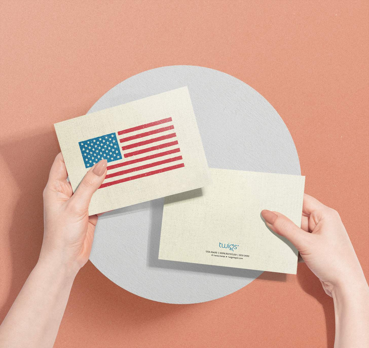 Woman holding two American flag cards showcasing the front and back