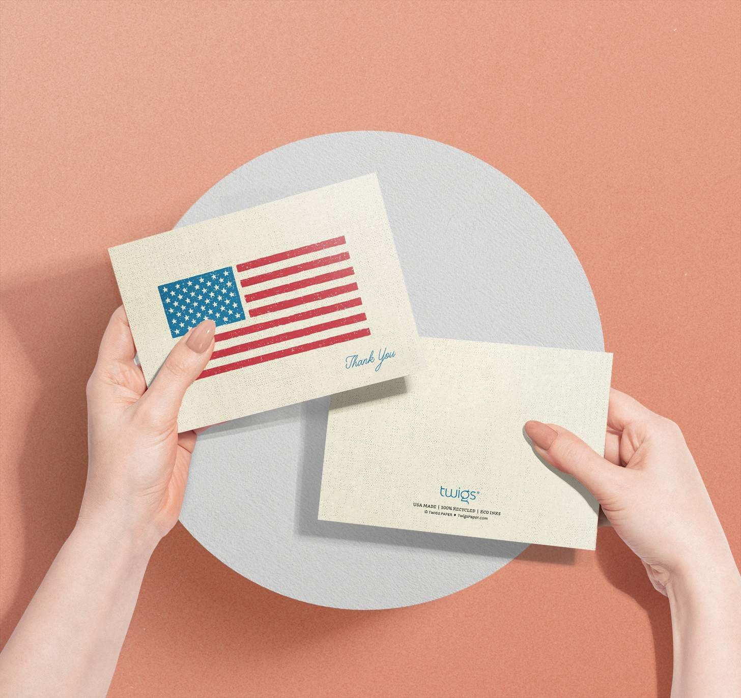 Woman's hands holding two American flag thank you cards showing the front and back