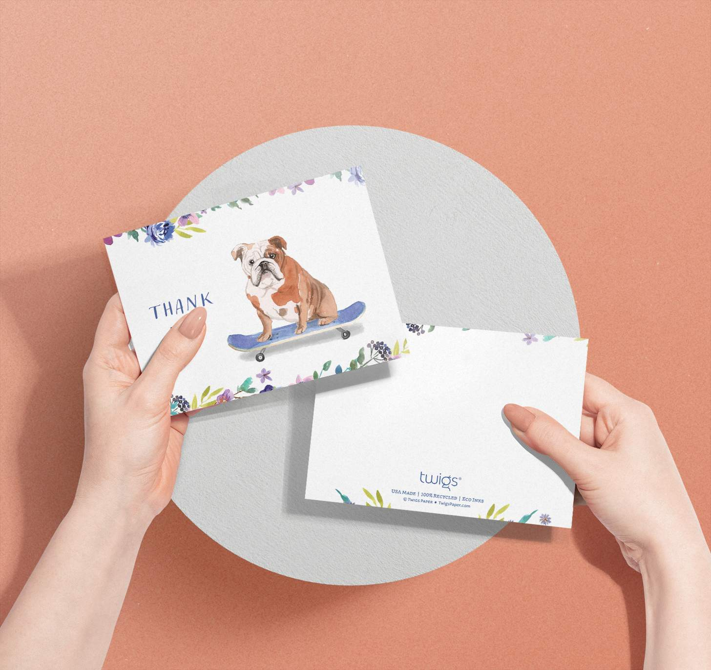 Woman's hands holding card with brown and white dog riding skateboard design