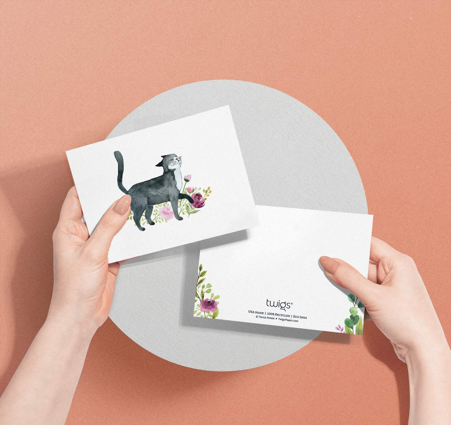 Hands holding black and white cat with flowers design card