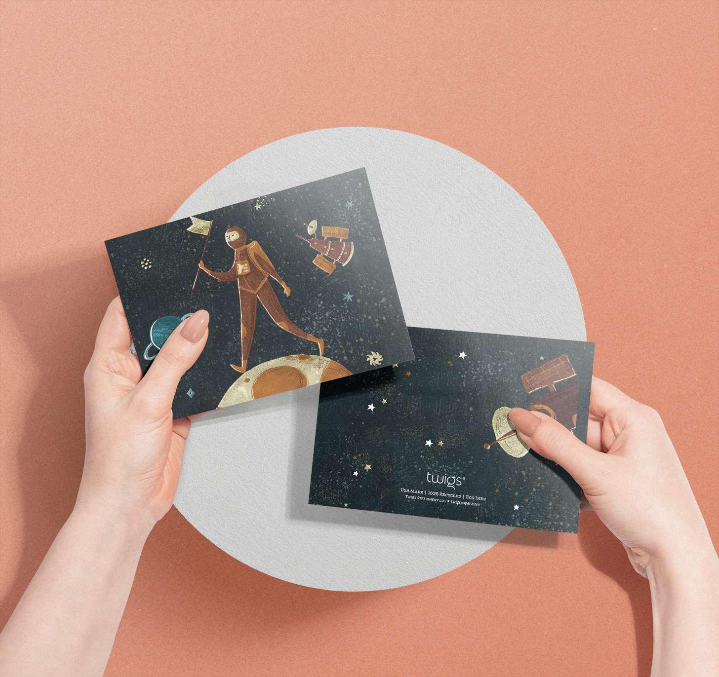 Woman's hand holding Astronaut on moon design card