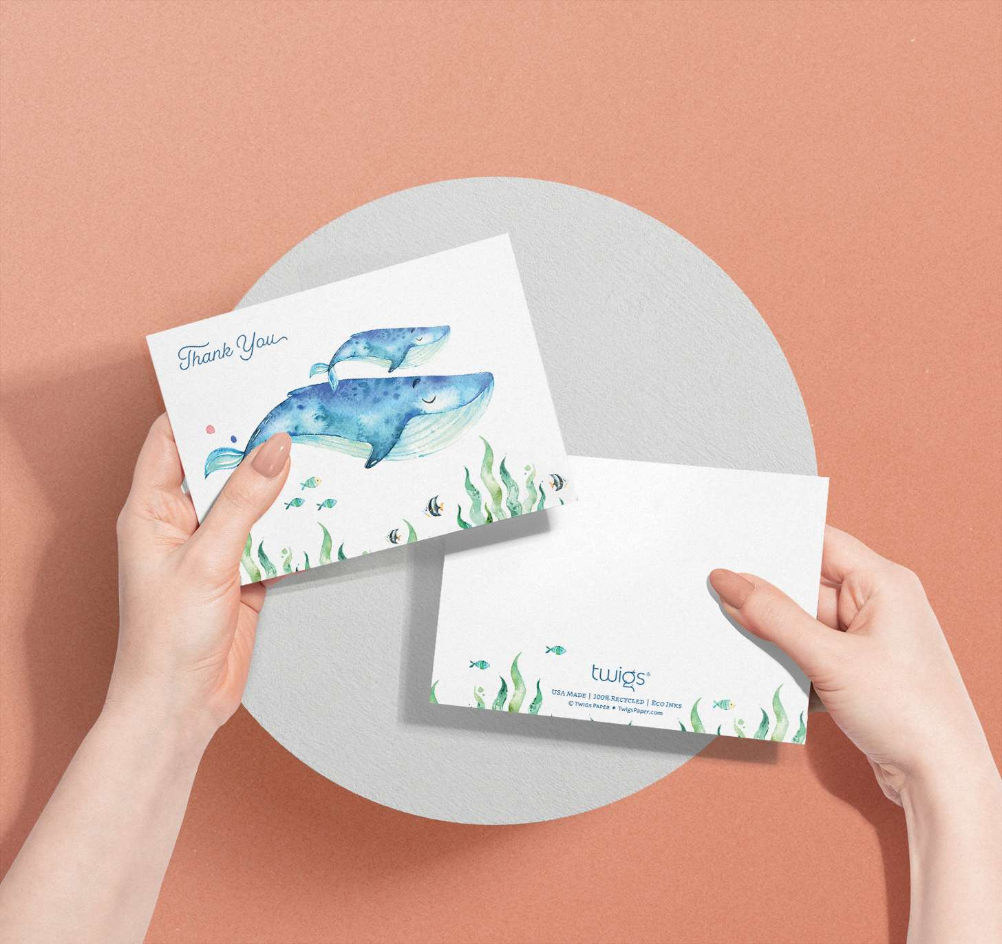 Woman's hands holding Mother and baby blue whale cards with tropical fish