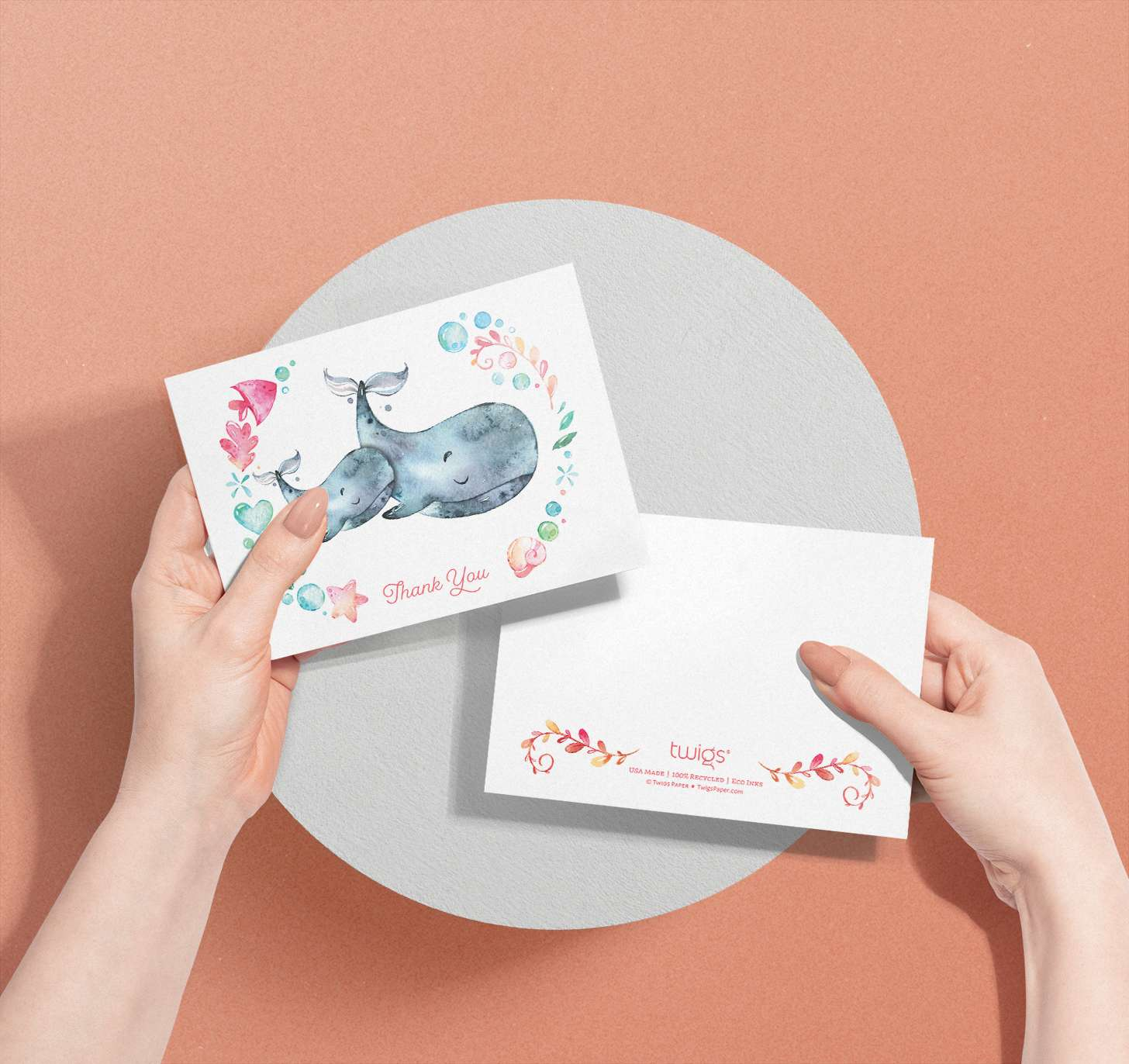 Woman's hands holding Mother and baby Gray whale cards with nautical border