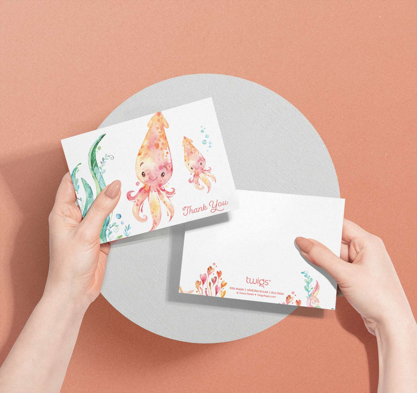 Woman's hands holding Mother and baby orange squid cards