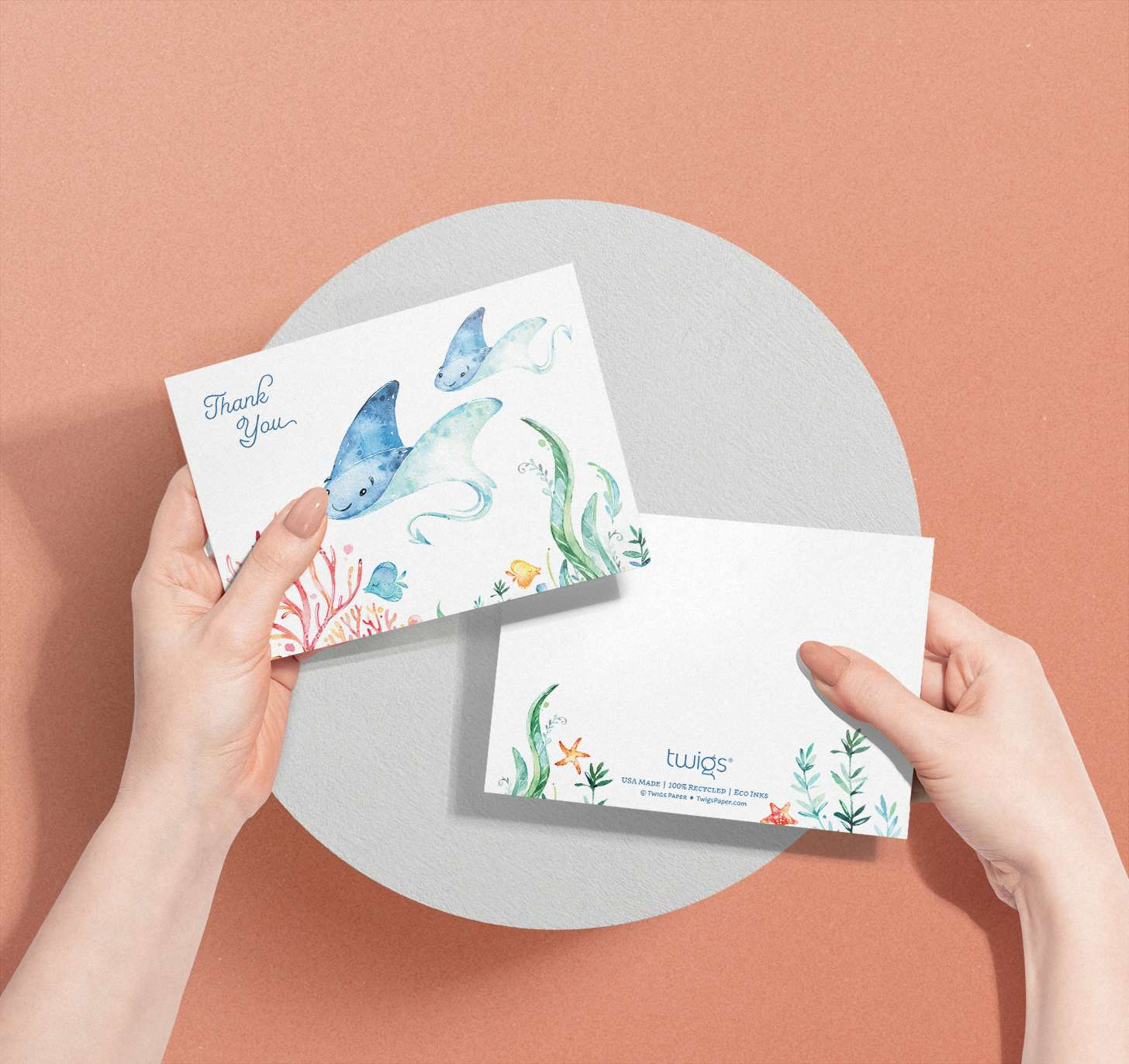 Woman's hands holding Mother and baby blue sting ray cards with tropical fish