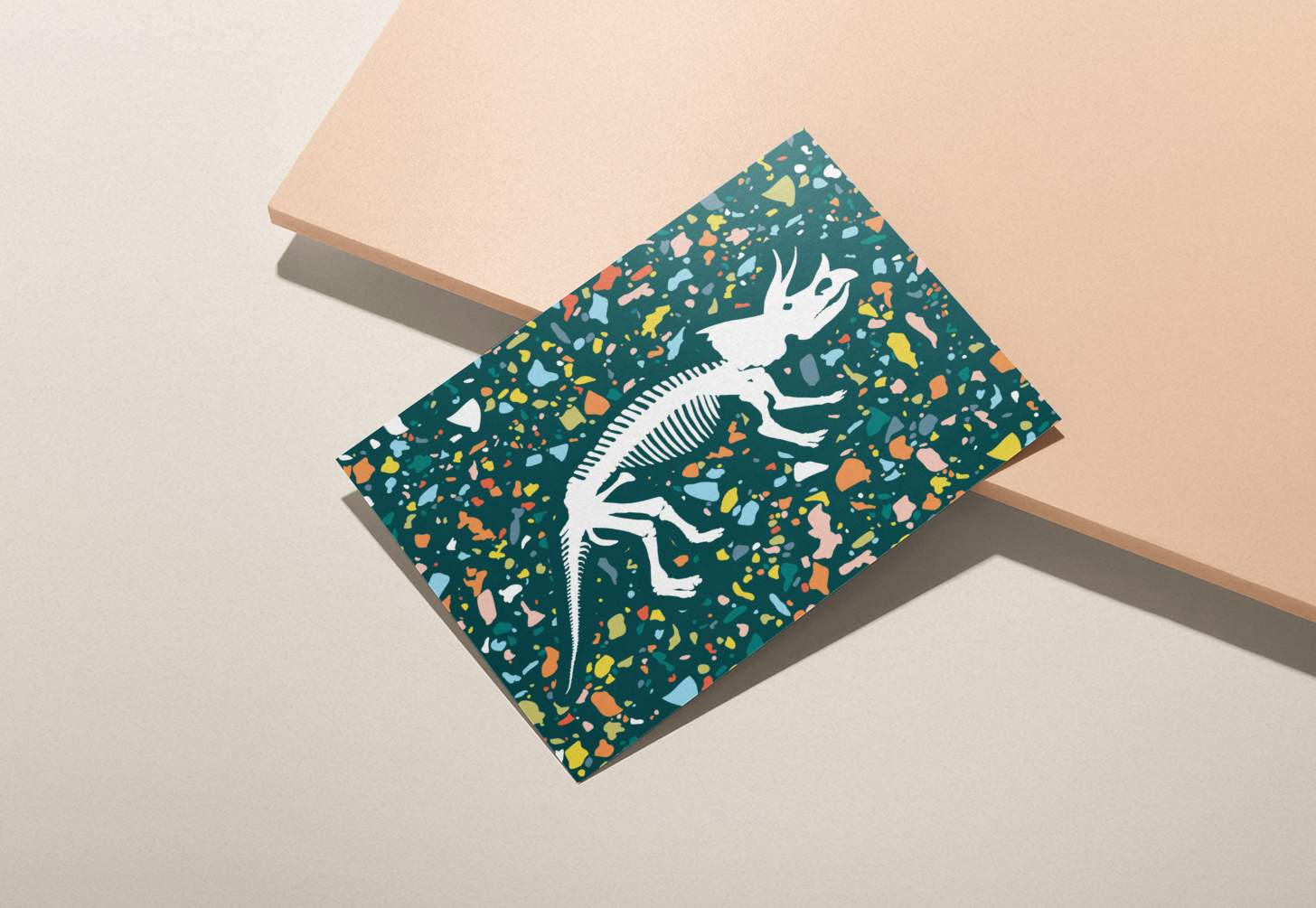 Dinosaur bones design with colorful green background card on pink background