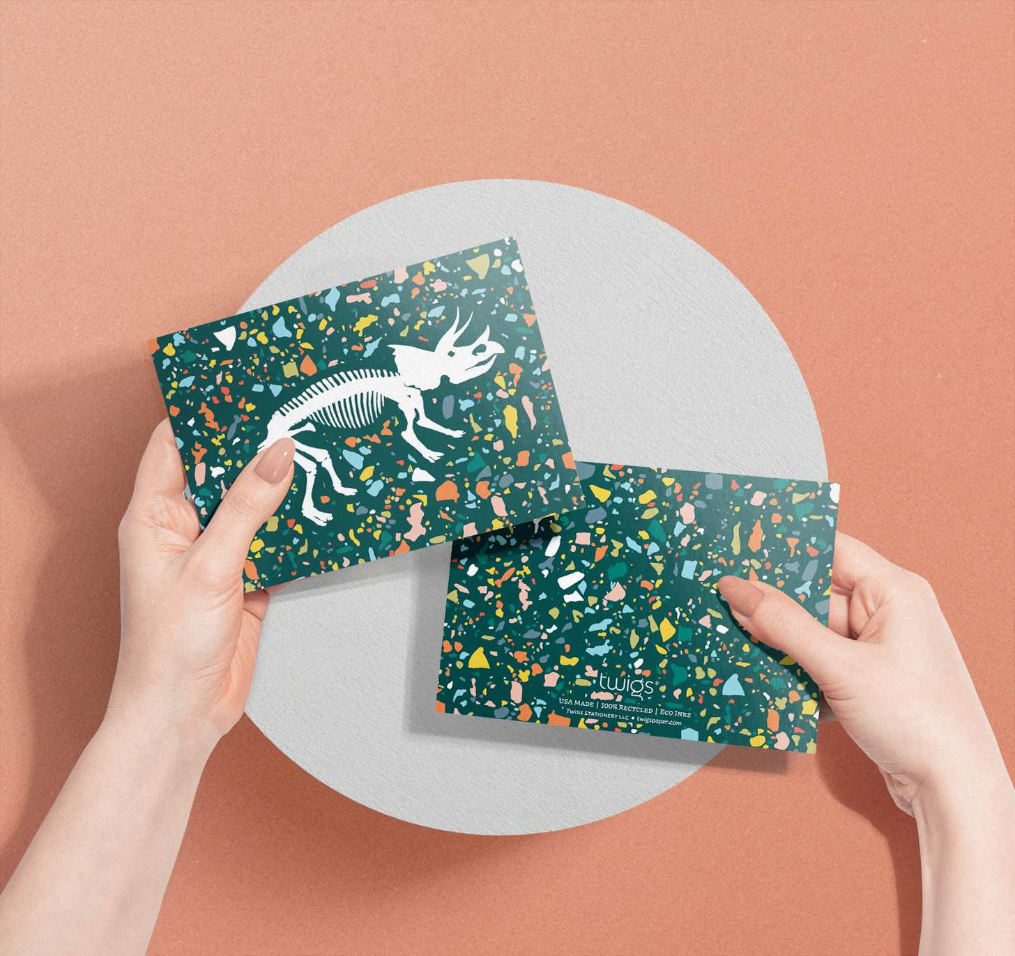 Woman's hand holding dinosaur bones design with colorful green background card