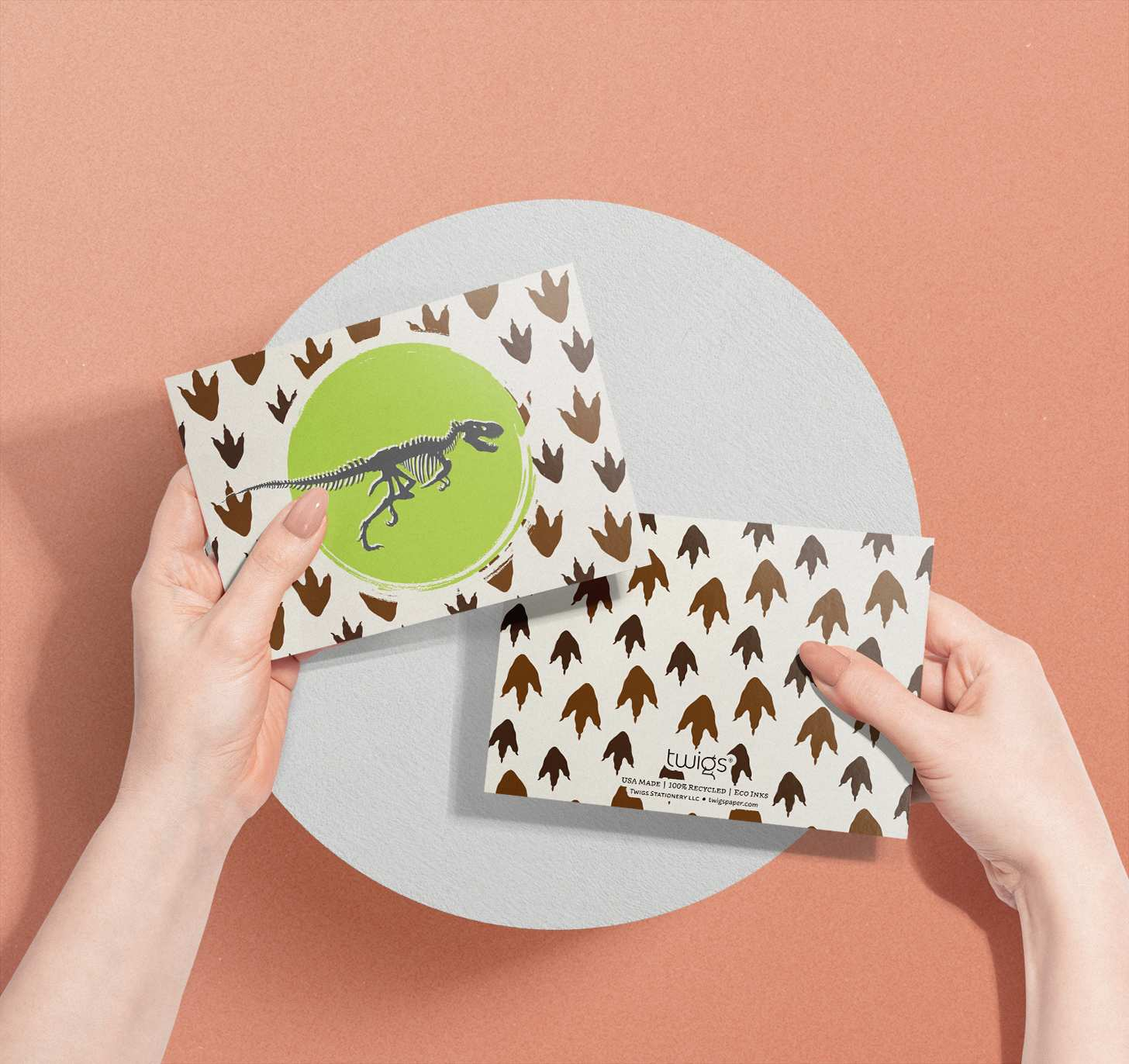 Woman's hand holding T-Rex bones with footprints design card