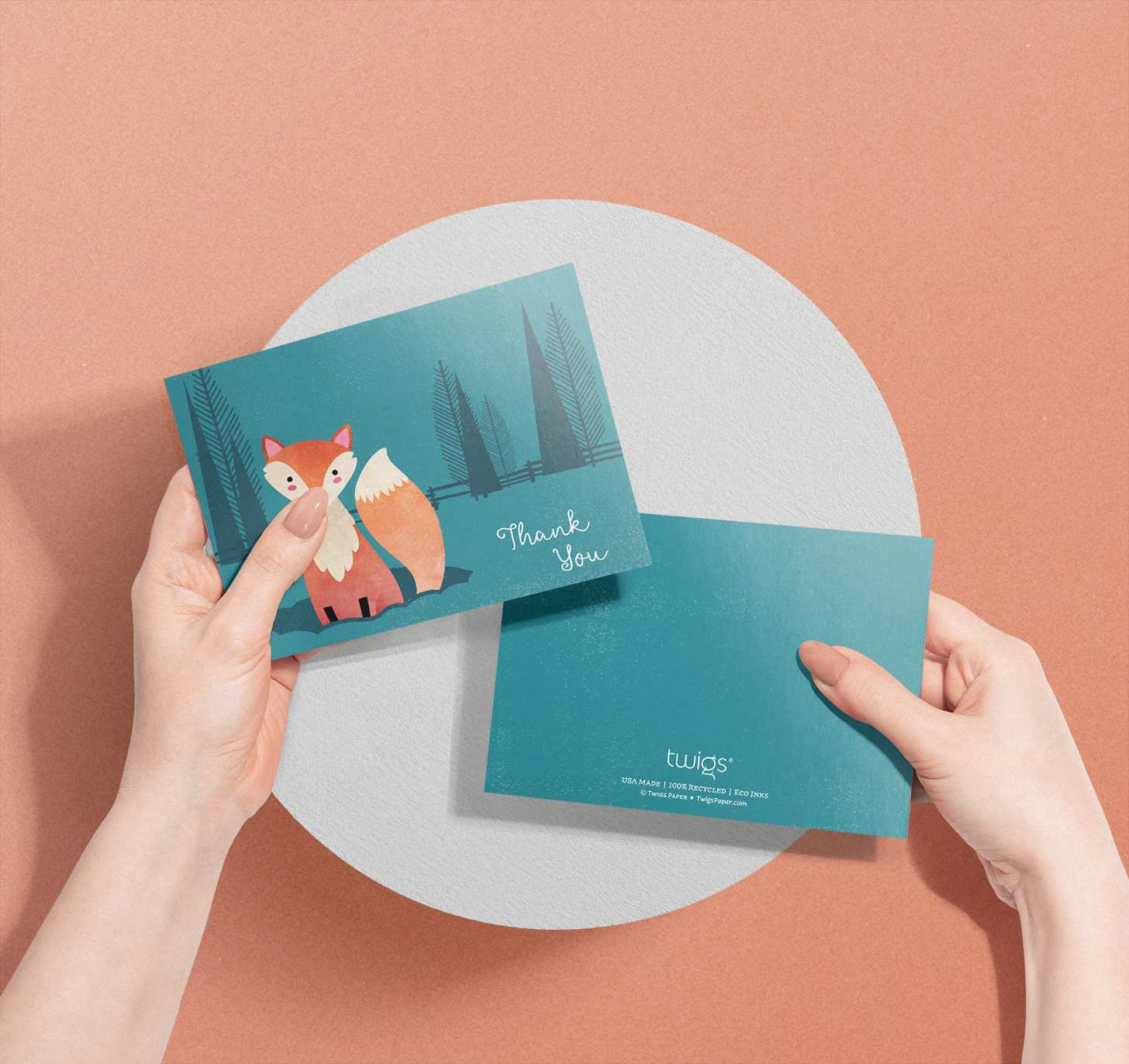 Woman's hands holding card with cute orange fox in blue forest design