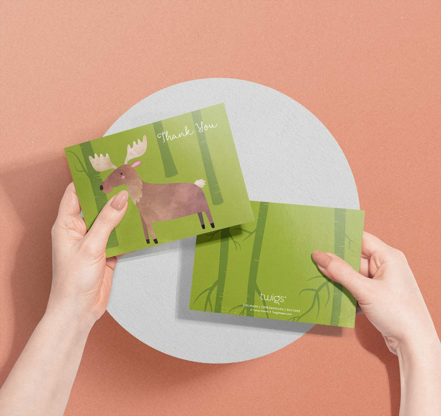 Woman's hands holding card with cute brown moose on green forest design