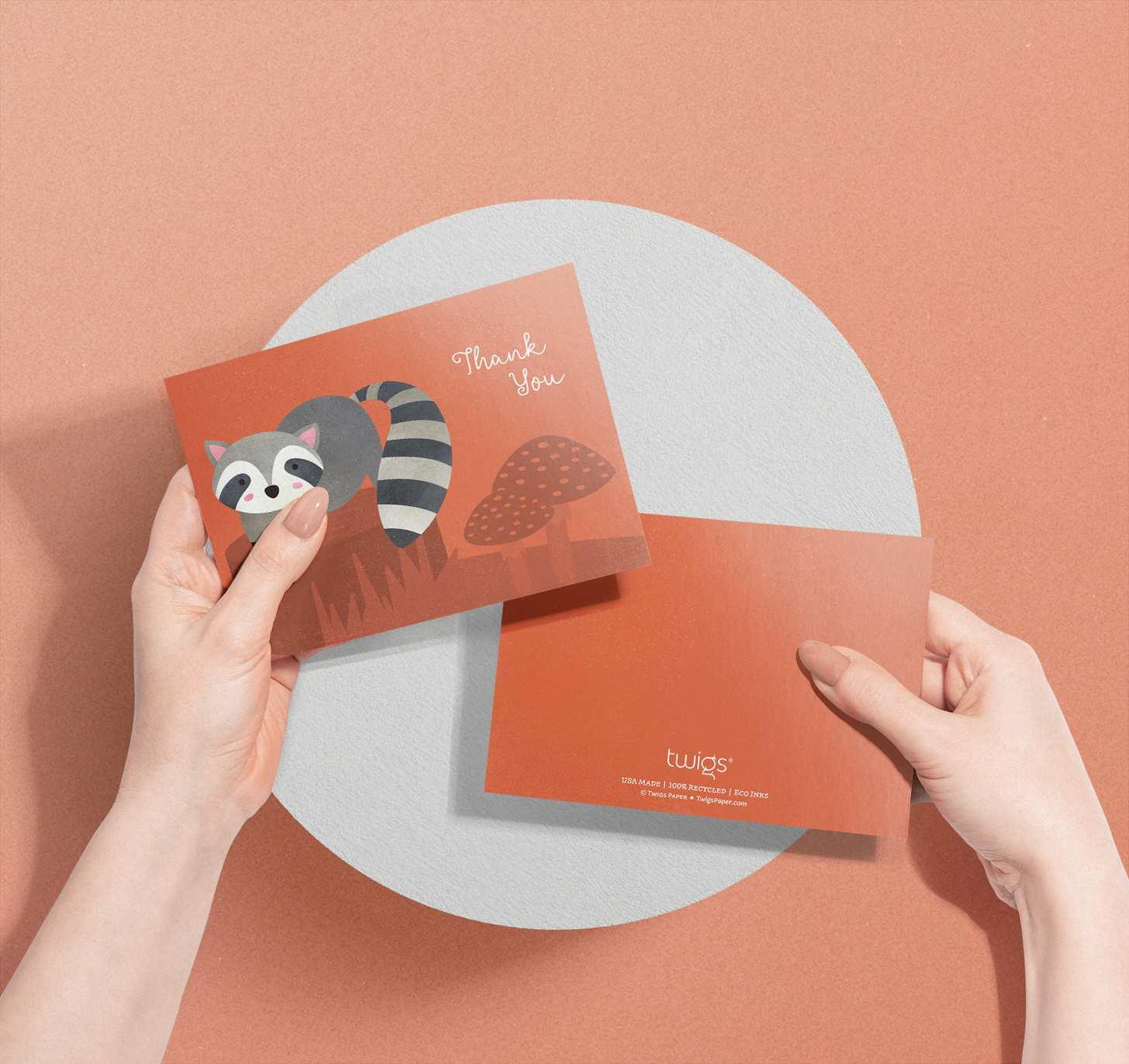Woman's hands holding card with cute grey raccoon on orange forest design