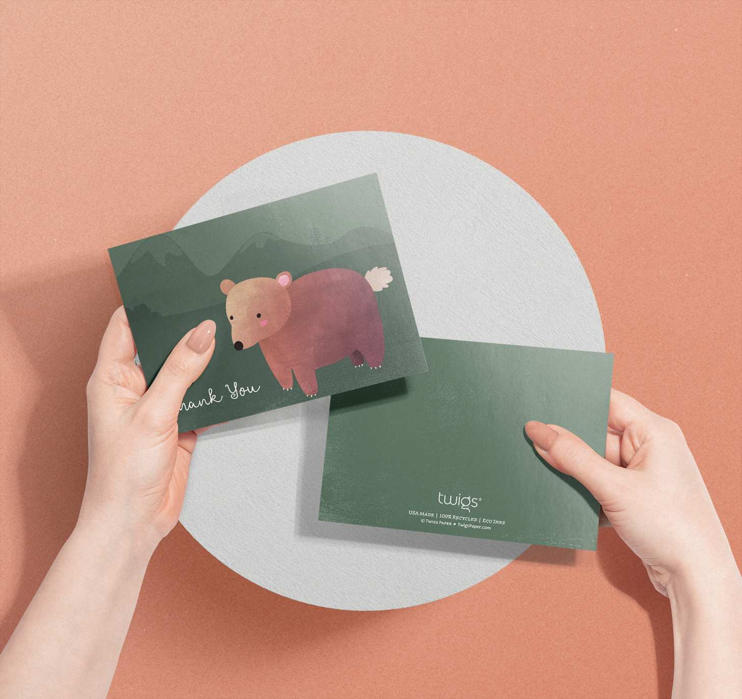 Woman's hands holding card with cute brown bear on green mountain design