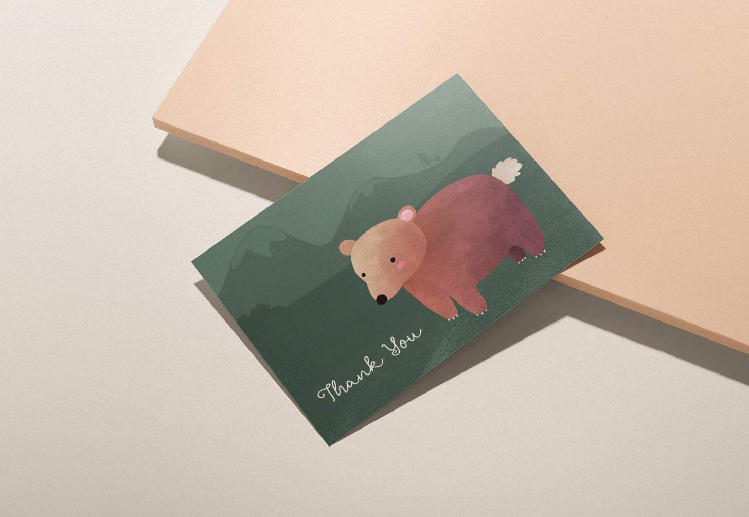 Cute brown bear on green mountain design on pink background